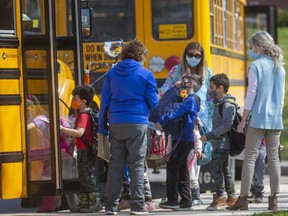 Students get on their school buses at Eagle Heights public school in London on Wednesday April 7, 2021. Even though there's been a provincewide stay-at-home order announced, local school board officials said that schools will remain open for in-class learning. (Mike Hensen/The London Free Press)
