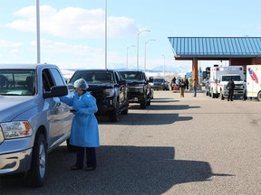 A health worker talks to a driver on the U.S. side of the Carway Border crossing in Montana as cars carrying First Nations members and other Albertans lined up to take advantage of free COVID shots from Montana's Blackfeet Nation April 21.