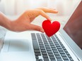 Girl hand take red heart at laptop keyboard for social online love chat and sharing encouragement over internet to fight Covid-19 virus together.