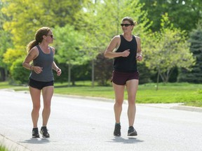 Michelle Pink and Vanessa Kinsley run through the late afternoon heat in London.  Both are long-time runners who ran the virtual half-marathon for the Forest City Road Races this spring and were doing a five-kilometre run on this day. Photograph taken on Friday May 21, 2021. (Mike Hensen/The London Free Press)