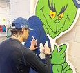 Toronto Maple Leafs star Auston Matthews signs an 2.4-metre Grinch wearing a  Leafs jersey that will be auctioned to raise money for Emmett Gervason to have an operation in California in July. Emmett was born with a congenital ear deformity. His grandfather, who lives in Chatham, came up with idea to make the Grinch and try to get it signed. (Supplied photo)