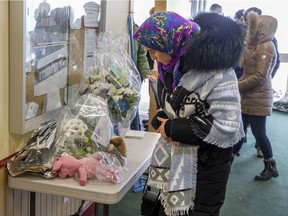 A woman looks at flowers dropped off by well wishers at the Centre Culturel Islamique de Québec in Quebec City in February 2017 after people were allowed back inside for the first time following a mass shooting that killed six Muslims.