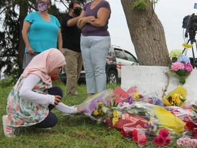 Nine-year-old Shahed Mahmoud places a flower arrangement at the corner of Hyde Park and South Carriage roads, where an impromptu memorial was created for the members of a Muslim family killed Sunday night. (JONATHAN JUHA/The London Free Press)