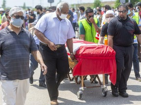 Four Canadian flag-draped coffins for the members of the Afzaal family, killed last Sunday when a vehicle jumped a curb at an intersection and struck them in what police allege was a deliberate attack, are wheeled to the front of a large crowd that gathered Saturday at the Islamic Centre of Southwest Ontario for an outdoor funeral.  Photograph taken on Saturday June 12, 2021. (Mike Hensen/The London Free Press)
