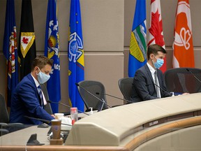 Calgary City Councillors Jeff Davison and Jeromy Farkas were photographed during the council vote to rescind the mandatory masking bylaw in the city. Mandatory masking for transit and inside city owned and operated facilities will remain for the time being. Council voted on Monday, July 5, 2021.