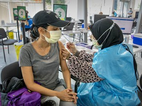 """""""The world is edging toward 5 million deaths from COVID-19,"""" Lise Ravary writes. """"When are we all going to get the message?"""" Above: Nurul Akidah Lukman administers a dose to Daisy Salgado at a COVID-19 vaccination site on Park Ave."""