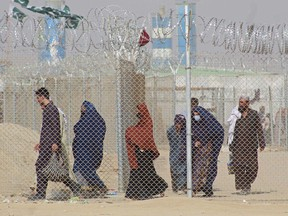 Afghan nationals walk along a fenced corridor as they enter Pakistan through the Pakistan-Afghanistan border crossing point in Chaman.