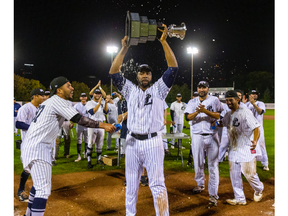 Slugger Cleveland Brownlee holds aloft the Dominico Cup as the London Majors celebrate their first Intercounty Baseball League title since 1975 after an 8-4 Game 5 win Friday night over Toronto at Labatt Park. (Mike Hensen/The London Free Press)