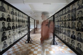 A tourist looks at portraits of victims of the Khmer Rouge at the Tuol Sleng genocide museum in Phnom Penh on February 2, 2009. Up to two million people were executed or died of starvation and overwork as the Khmer Rouge dismantled modern Cambodian society during its rule in a bid to forge a communist utopia.  (TANG CHHIN SOTHY/AFP/Getty Images)