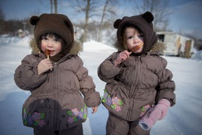 3 year old twins , Charlotte (left) and Reilly Gunning (right) enjoy maple taffy at the annual winter festival in Dollard des Ormeaux's William Cosgrove Centennial Park  Sunday, February 9, 2014. (Peter McCabe / THE GAZETTE)