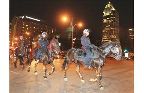 Mounted police ride down Rene Levesque Blvd. after Habs Stanley Cup series victory over the Bruins in Boston, in Montreal Wednesday May 14, 2014.