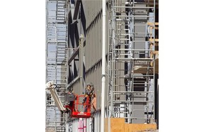 Soccer complex being built near the corner of Papineau Ave. and Louvain St. on Tuesday May 06, 2014. Picture shows worker on the north side of site working on outside wall of main building.