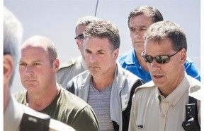 Left to right: Former Montreal, Maine & Atlantic Railway employees Thomas Harding, Jean Demaître and Richard Labrie (in blue) arrive at a courthouse in Lac-Mégantic on Tuesday, May 13, 2014. The three have been charged with 47 counts of criminal negligence causing death.