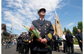 A firefighter from Maine stands with colleagues outside the Ste-Agnès church in Lc-Mégantic, Sunday, July , 2014, during a mass to mark the first anniversary of the trian disaster in that town.  The mass was done as part of weekend activities to commemorate the tragedy.