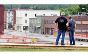 Standing on a new boardwalk, visitors look out at the former downtown core of Lac-Mégantic on Saturday. June 28.