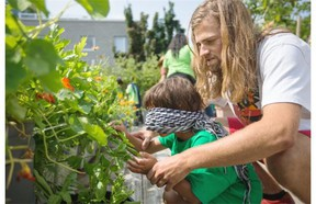 Urban agriculture intern at Santropol Roulant Marc Antoine Fortin teaches a child to identify plants with touch during an urban agriculture workshop for children at the Santropol Roulant building in Montreal.