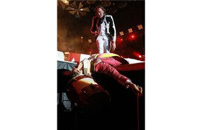 """Win Butler of the Montreal band Arcade Fire looks down at a """"collapsed"""" drummer figure with a papier mache head during the band's concert at Parc Jean-Drapeau in Montreal on Saturday."""
