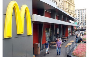 People walk in front of a closed McDonald's restaurant, the first to be opened in the Soviet Union in 1990, in Moscow on August 21, 2014. Russian consumer-safety regulators have ordered 12 of the chain's restaurants to temporarily close, including its highest-profile locations, and locals are increasingly turning against the U.S. company.
