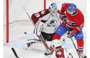 Canadiens' Michael Bournival watches the puck go wide past Avalanche goalie Reto Berra and defenceman Zach Redmond at the Bell Centre on Thursday night.