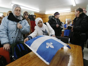 Montrealer Dr Najat Boughaba lays down a Quebec flag at her table on her arrival with several other Muslim women at the  Age d'Or Club in Hérouxville, Qc Sunday, February 10, 2007. The women came to the town to discuss town councillor André Drouin's rules for would-be immigrants and to bring residents gifts. The town council had passed a list of societal norms for would-be immigrants  - particularly Muslims -  saying, for instance, a man cannot stone a woman to death or burn her with acid and faces are not to be covered except at Halloween.