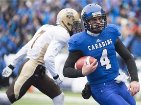 Montreal Carabins quarterback Gabriel Cousineau breaks away from Manitoba Bisons' Jayden McKoy to score a touchdown during first half CIS university football semifinal action in Montreal, Saturday, November 22, 2014.