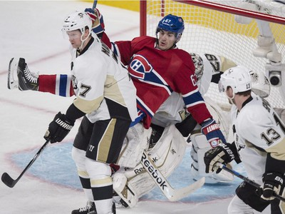 Max Pacioretty falls onto Pittsburgh Penguins goalie Marc-Andre Fleury during second-period action Tuesday, Nov. 18, 2014, in Montreal.