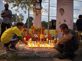 Gilberto Villanueva, (right) Fredy Villanueva's father, lights candles  at a vigil commemorating the 5th anniversary of the shooting of her son in Montreal-North area of  Montreal Friday Aug. 9, 2013.