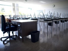 An empty teacher's desk is at the front of an empty classroom.