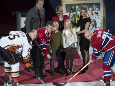 Former Montreal Canadiens captain Saku Koivu, surrounded by family members, drops the puck between Anaheim Ducks' Ryan Getzlaf and Montreal Canadiens' Andrei Markov during a ceremony honouring his career, Thursday, December 18, 2014 in Montreal.