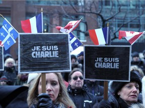 """Women hold placards reading, Je Suis Charlie (I am Charlie) during a solidarity rally on January 11, 2015 in Montreal to honor the 17 victims of a three-day killing spree by homegrown Islamists. About 25,000 people marched Sunday in Montreal in solidarity with France and in memory of 17 people killed in jihadist attacks in Paris, organizers said. Montreal Mayor Denis Coderre and several Quebec officials joined the French consul general Bruno Clerc at the head of a long procession by marchers waving Canadian, French and Quebecois flags, as well as signs bearing the message """"Je Suis Charlie."""