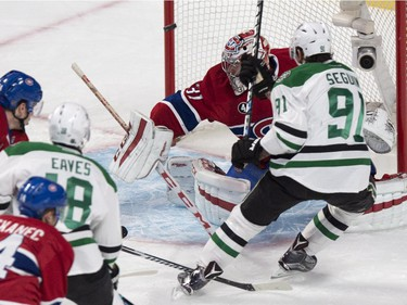The puck goes off the goal post behind Montreal Canadiens goalie Carey Price on a shot by Dallas Stars' Tyler Seguin during first period NHL hockey action Tuesday, January 27, 2015 in Montreal.
