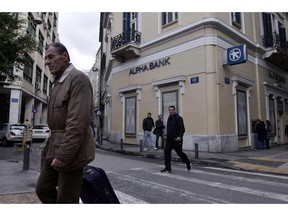 People walk past an Alpha bank branch in central Athens on January  29, 2015. Economic powerhouses Germany and China warned Greece on January 29 against reneging on reforms tied to its massive international bailout, with markets still jittery over fears Athens could default on its debt.