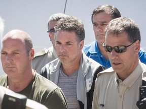Left to right: Former Montreal, Maine & Atlantic Railway employees Thomas Harding, conductor for the train that derailed and exploded in Lac-Mégantic on July 6, 2013 killing 47 people, Jean Demaître, and Richard Labrie (in blue) arrive at a courthouse in Lac-Mégantic, 270 kilometres east of Montreal on Tuesday, May 13, 2014.