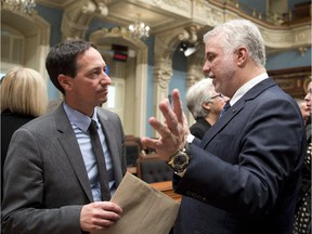 """Quebec Premier Philippe Couillard, right, and Quebec Opposition Leader Stephane Bedard chat after they exchanged season's greetings as the fall session comes to an end Friday, December 5, 2014 at the legislature in Quebec City. Bedard suggested last week  that the premier was slow to act on a Quebec charter of secularism because he had been """"impregnated"""" by Saudi Arabian values."""