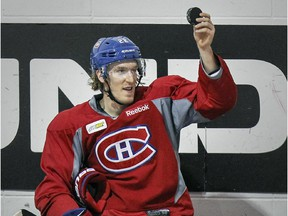 Canadiens forward Dale Weise holds up a puck that was fired into the bench during practice at the Bell Sports Complex in Brossard on Feb. 5, 2015.