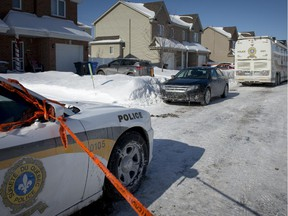 Sûreté du Québec vehicles outside the home where a 7-year-old girl was found dead and her mother in critical condition.
