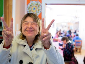 Helen Jolly flashes a peace sign on Saturday at Chez Doris, which has resumed its weekend services.