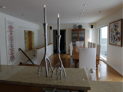 A view from the kitchen to the dining room area in the home of Anne Darche at the Habitat 67 complex in Montreal. In the foreground are silver branch candlesticks by American desiger Michael Aram.