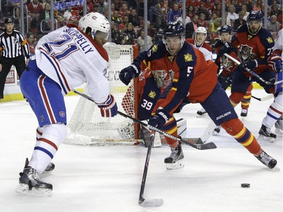 Montreal Canadiens right wing Devante Smith-Pelly (21) takes a shot as Florida Panthers defenseman Aaron Ekblad (5) defends during the first period Tuesday, March 17, 2015,  in Sunrise, Fla.