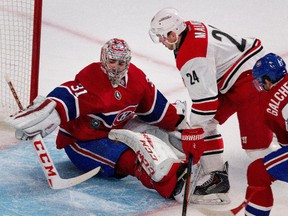 Montreal Canadiens goalie Carey Price makes a save against Carolina Hurricanes centre Brad Malone as Montreal Canadiens right wing Brendan Gallagher tries to clear him from the goal crease at the Bell Centre on Thursday, March 19, 2015.