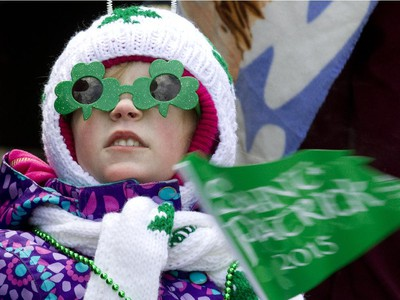 Six-year-old Bethany Vienneau watches a passing float during the annual St. Patrick's parade along Ste- Catherine St. in Montreal on Sunday March 22, 2015.
