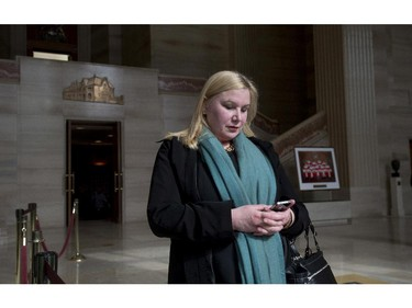 Wendy Cukier reads a message on her smart phone as she stands in the foyer of the Supreme Court of Canada in Ottawa, Friday March 27, 2015. Cukier is president of the Coalition for Gun Control.