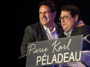 Pierre Karl Péladeau, left, hugs Bernard Drainville after Drainville gave a speech supporting Pierre Karl Péladeau for the leadership of the party at a leadership rally in Montreal on Saturday May 9, 2015.
