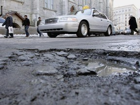 Motorists steer past a pothole on a Montreal street. In the last few years, the city has steadily increased its spending to repair and improve roads and water infrastructure. In 2015, it spent a record $445 million, and expects to pay out a similar amount in 2016.