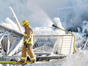 Firefighterwalks past a hose pouring water on the smouldering remains of a seniors residence in L'Isle-Verte on Jan. 23, 2014.