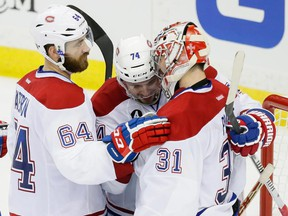 Canadiens goalie Carey Price is congratulated by teammates Greg Pateryn (No. 64) and Alexei Emelin after beating the Lightning 6-4 in Game 4 of Eastern Conference semifinal series on May 7 in Tampa, Fla.