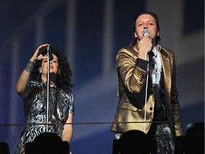 Arcade Fire performs outside the iconic Capitol Records building in Hollywood, California October 29, 2013.  Arcade Fire, led by Win Butler (R) and Régine Chassagne (L),  staged an impromptu concert to mark the release of their new album Reflektor.