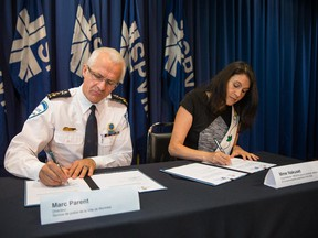 Montreal police chief Marc Parent signs a document alongside Nakuset, co-president of the RESEAU pour la strategy urbaine de la communauté autochtone à Montreal, during a press conference Thursday at SPVM headquarters, about a new agreement between Montreal's aboriginal community and police .