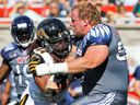 Alouettes centre Luc Brodeur-Jourdain is hit by Hamilton Tiger-Cats' Taylor Reed after losing his helmet during game in 2015.