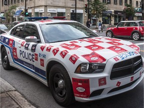 Police car plastered with stickers at the corner of Peel St. at de Maisonneuve Blvd. in July 2015.